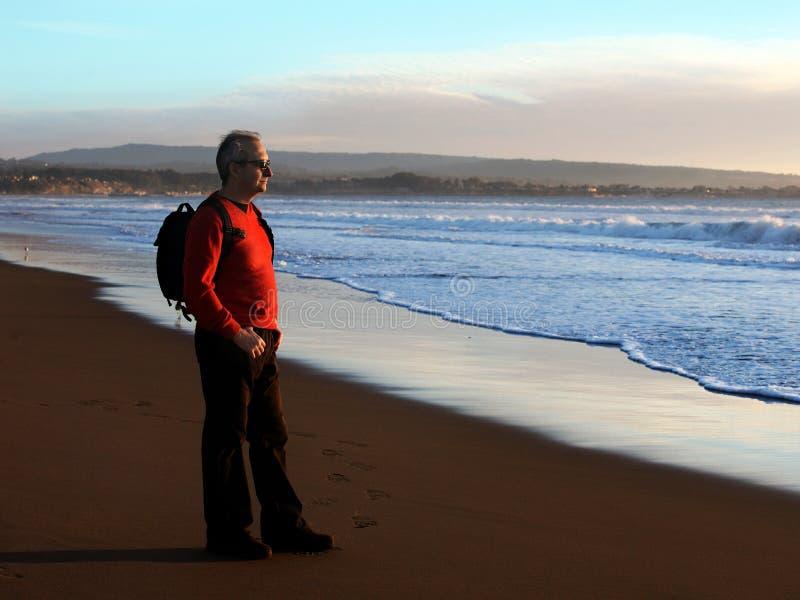 Homem que aprecia o por do sol pelo oceano fotografia de stock royalty free