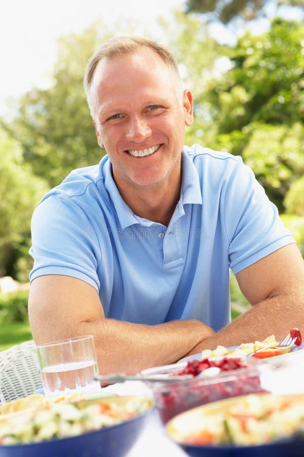 Homem que aprecia a refeição no jardim imagem de stock