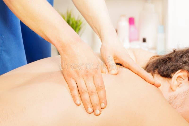 Homem que aprecia uma massagem profunda da parte traseira do tecido fotografia de stock royalty free