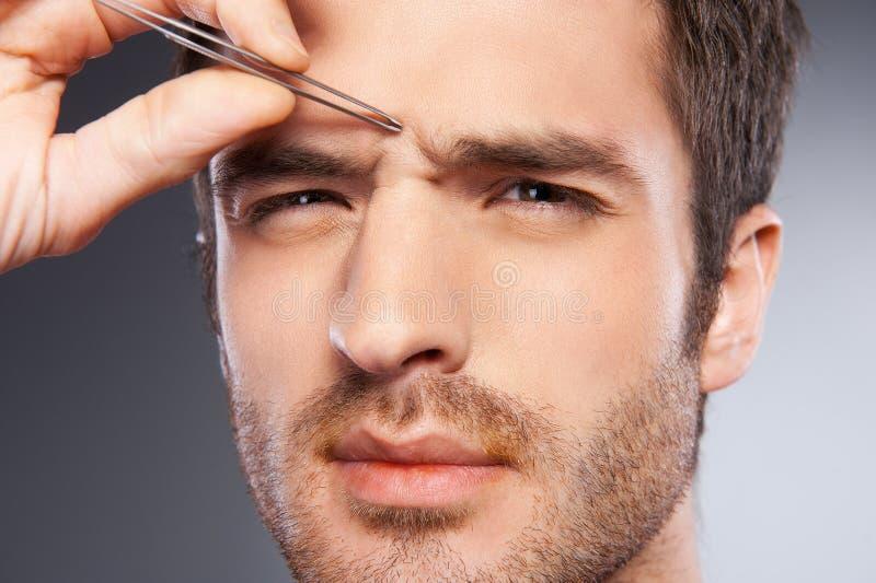 Homem que arranca as sobrancelhas. imagens de stock