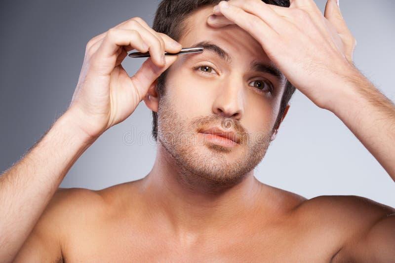 Homem que arranca suas sobrancelhas. imagens de stock