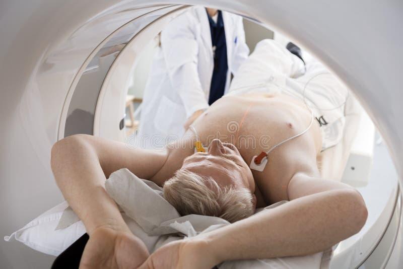 Homem que atravessa a varredura do CT no hospital foto de stock