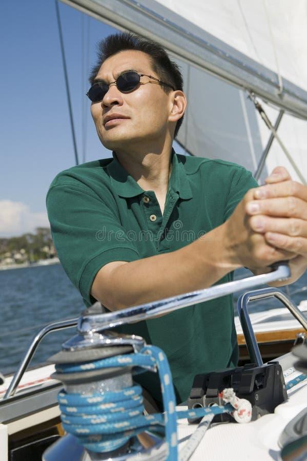 Homem que aumenta a vela no veleiro fotografia de stock royalty free