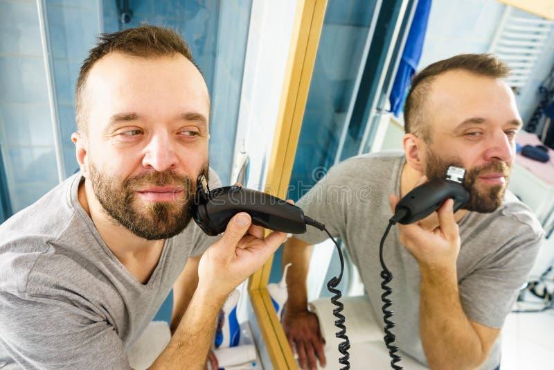 Homem que barbeia aparando sua barba fotos de stock