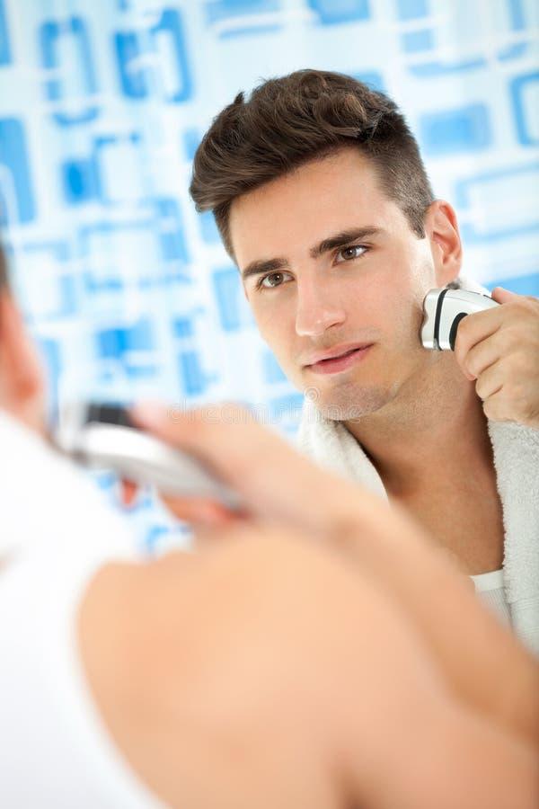Homem que barbeia a barba com barbeador bonde imagem de stock royalty free