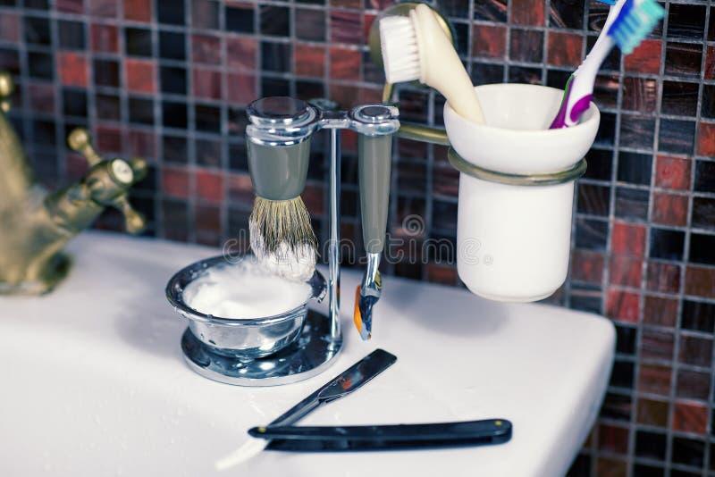 Homem que barbeia a lâmina de segurança dos acessórios, a lâmina reta, o copo com espuma e as escovas no dissipador, fundo da tel imagens de stock royalty free