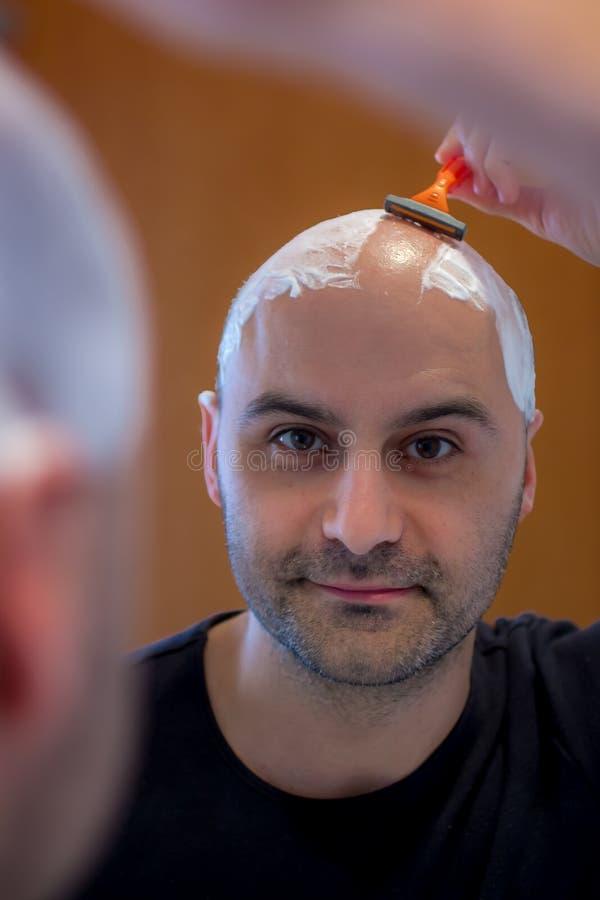 Homem que barbeia sua cabeça imagens de stock royalty free