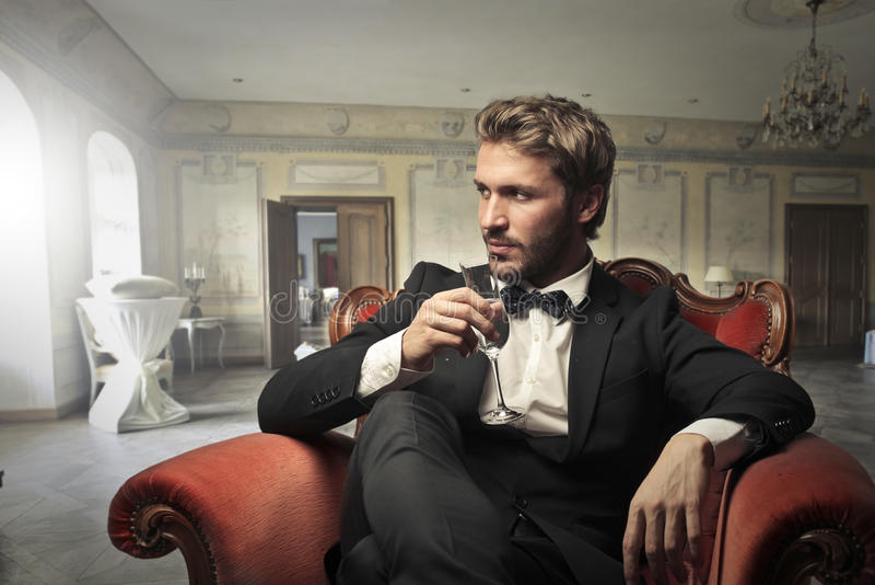 Homem que bebe na sala de visitas fotografia de stock royalty free