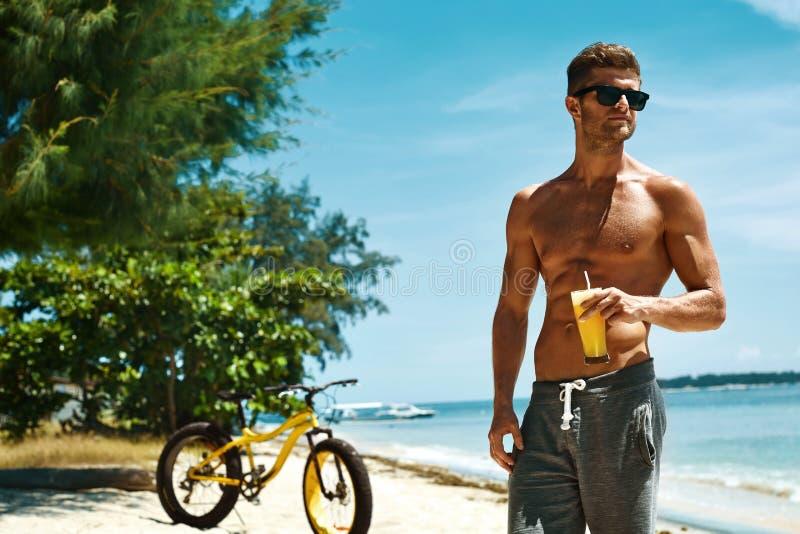 Homem que bebe a praia de Juice Smoothie Cocktail On Summer férias fotografia de stock