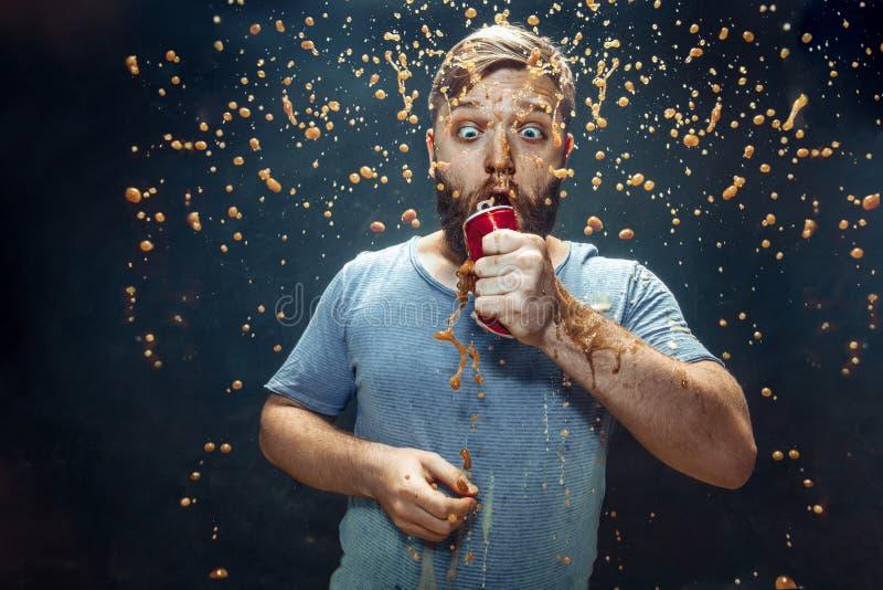 Homem que bebe uma cola e que aprecia o pulverizador fotografia de stock