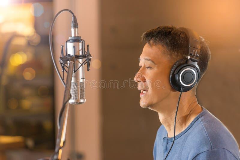 Homem que canta na frente do microfone da gravação foto de stock