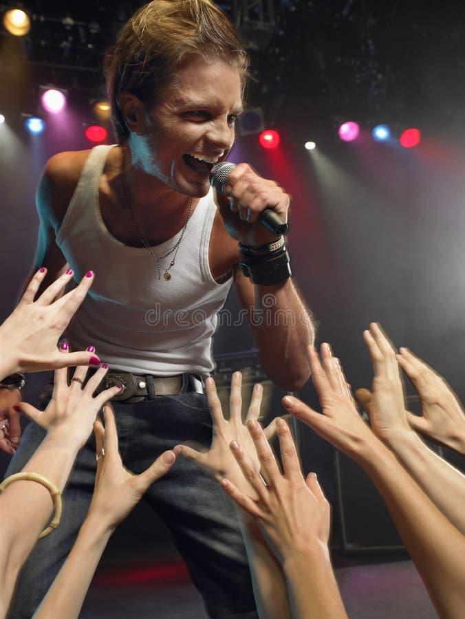 Homem que canta perto dos fãs adoradores fotografia de stock