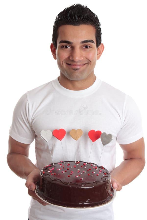 Homem que carreg o bolo romântico do coração foto de stock