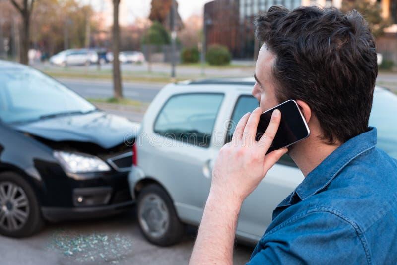 Homem que chama a emergência da borda da estrada após o acidente de trânsito imagem de stock