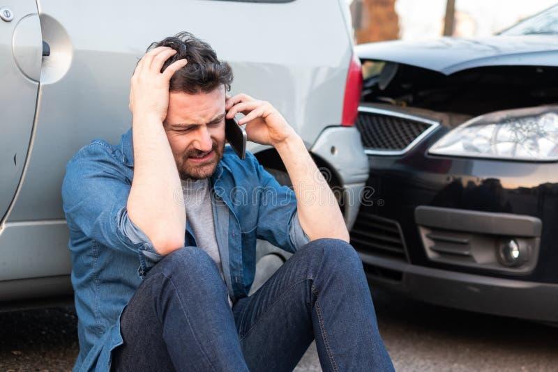 Homem que chama a emergência da borda da estrada após o acidente de trânsito fotografia de stock
