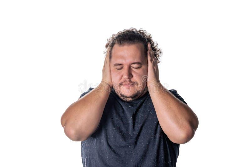 Homem que cobre suas mãos do witn das orelhas, fechando seus olhos, isolados no fundo branco Não ouça nenhum conceito mau imagem de stock