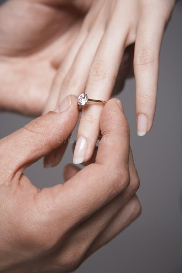 Homem que coloca o dedo de Ring In Woman do acoplamento imagem de stock royalty free
