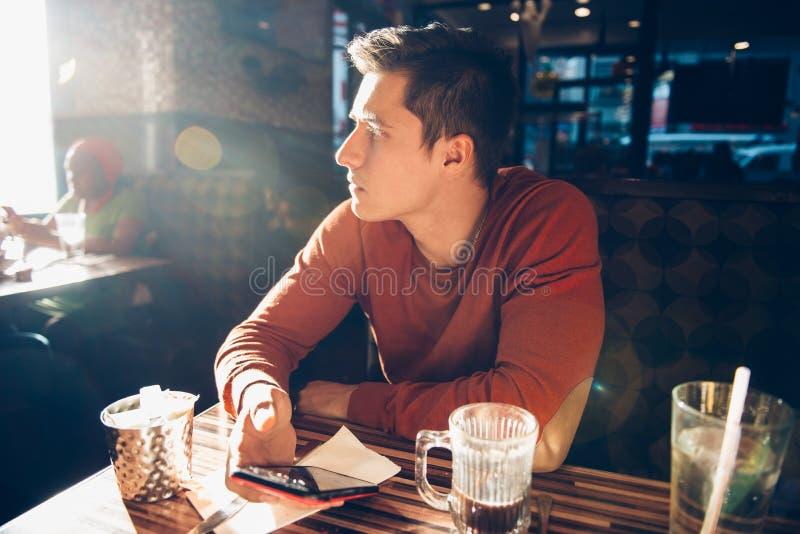 Homem que come o café da manhã da manhã com café no café do jantar e que usa seu telefone celular fotografia de stock
