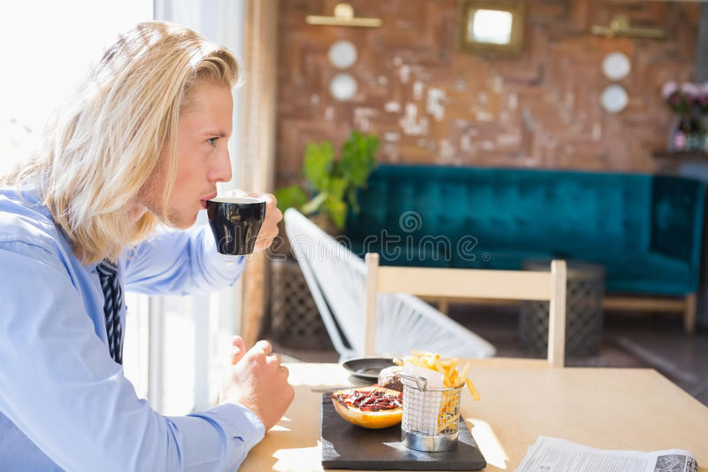 Homem que come o café e o café da manhã imagem de stock
