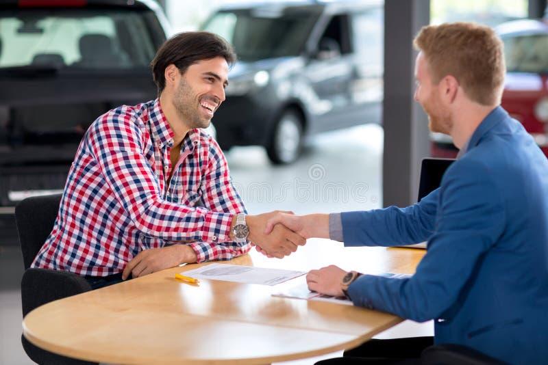 Homem que compra um carro no negócio lhes estão agitando as mãos para fechar t fotos de stock