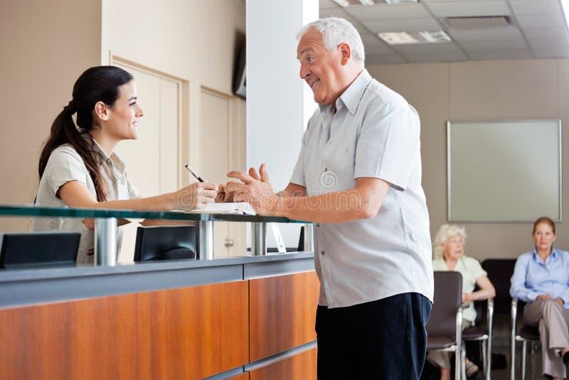 Homem que comunica-se com o recepcionista fêmea imagens de stock royalty free