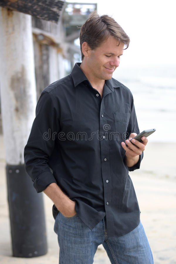Homem que comunica-se com o telefone esperto na praia fotografia de stock royalty free