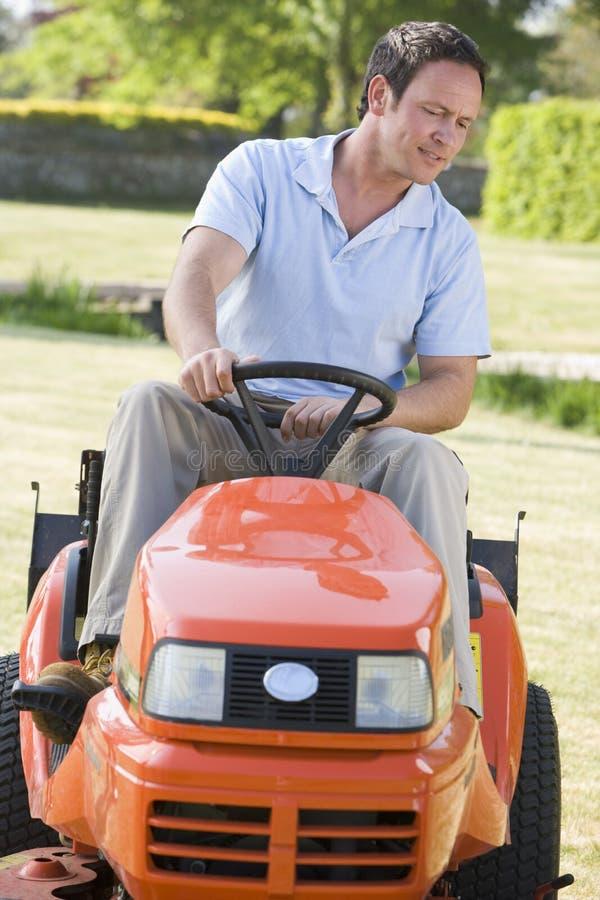 Homem que conduz ao ar livre o lawnmower fotos de stock royalty free