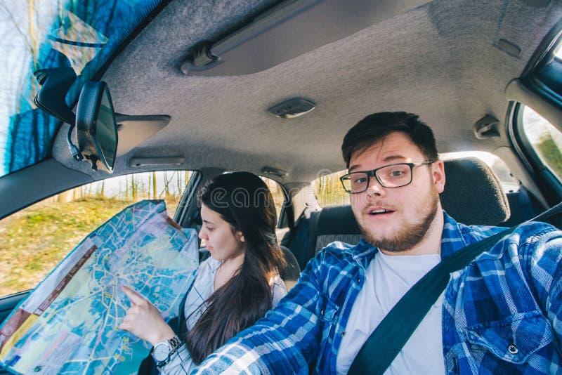 Homem que conduz o carro jovem mulher como o navegador ao lado dele Trave do carro foto de stock