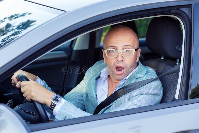 Homem que conduz um carro chocado aproximadamente para ter o acidente de tráfico, windsh imagem de stock