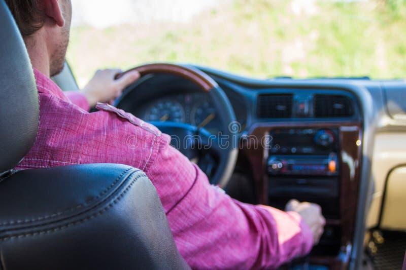 Homem que conduz um carro Mãos na transmissão fotografia de stock