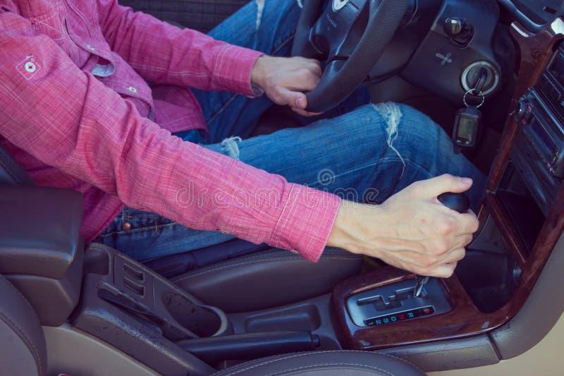Homem que conduz um carro Mãos na transmissão imagens de stock