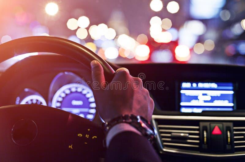 Homem que conduz um carro na noite foto de stock royalty free