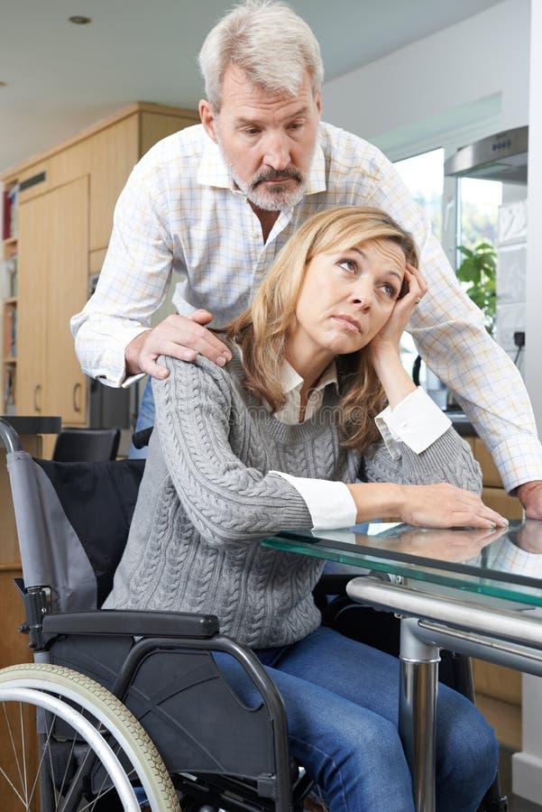 Homem que consola mulher deprimida na cadeira de rodas em casa imagem de stock