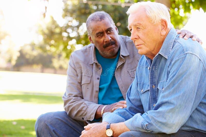 Homem que consola o amigo superior infeliz fora fotografia de stock royalty free