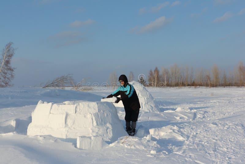 Homem que constrói um iglu de blocos da neve no inverno foto de stock royalty free