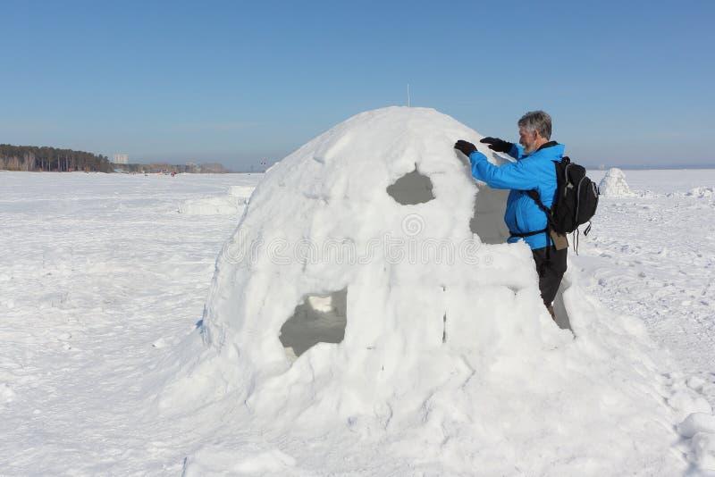 Homem que constrói um iglu no inverno fotos de stock
