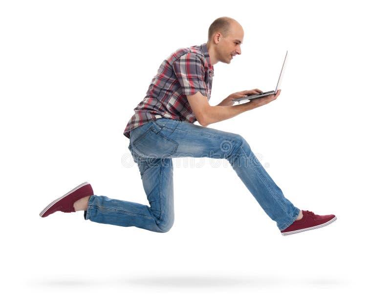 Homem que corre com um portátil imagem de stock