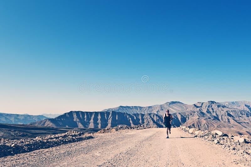 Homem que corre na estrada da montanha imagem de stock