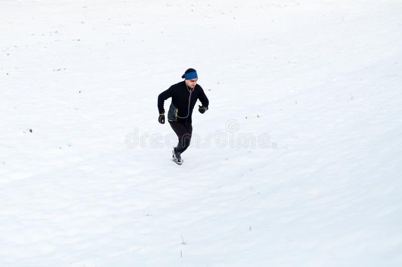 Homem que corre na neve imagem de stock royalty free