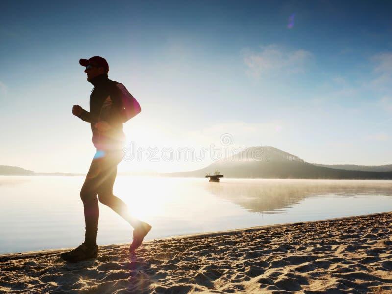 Homem que corre no tempo do crepúsculo do beira-mar Atleta do corredor que corre no beira-mar Silhueta da aptidão do desportista fotos de stock