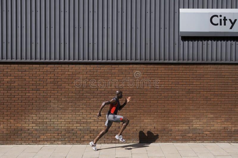 Homem que corre a parede de tijolo passada com 'a cidade' escrita nela imagem de stock