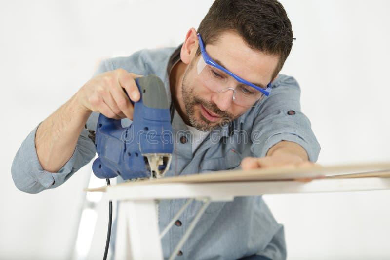 Homem que corta a madeira com m?quinas de tritura??o imagem de stock royalty free