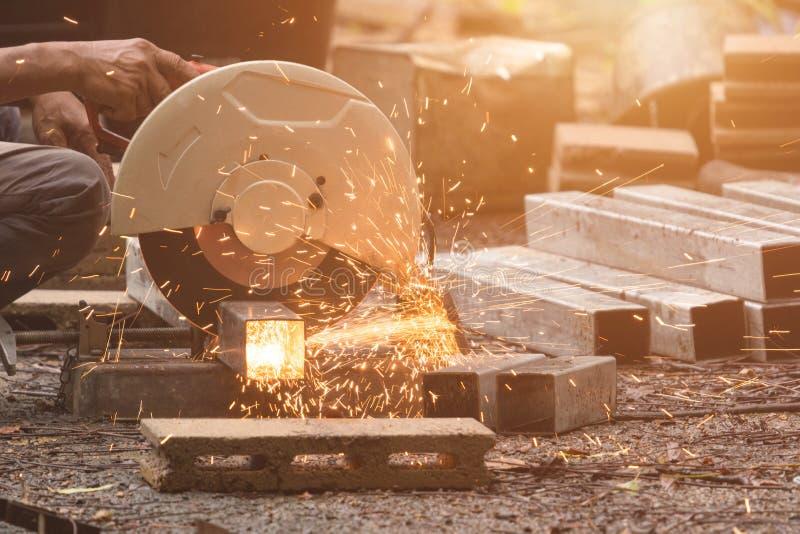 Homem que corta metal por meio de serra circular imagem de stock