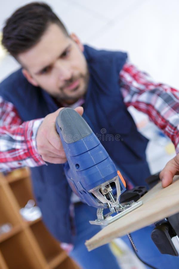 Homem que corta o bloco de madeira com serra tico-tico foto de stock