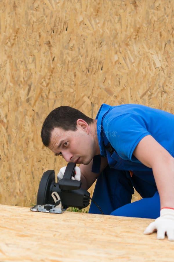 Homem que corta uma parte de madeira compensada com uma serra elétrica, vista dianteira imagens de stock