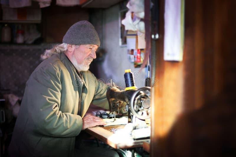 Homem que costura em casa imagens de stock royalty free