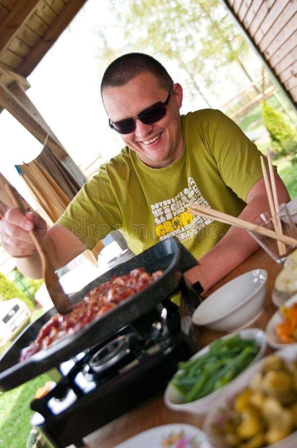 Homem que cozinha ao ar livre fotos de stock