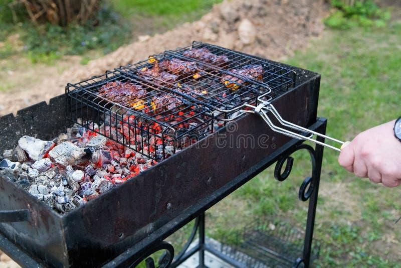 Homem que cozinha a carne no fogo da grade do assado fora fotos de stock