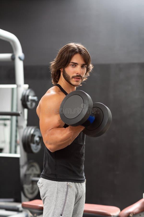 Homem que dá certo com pesos em um gym imagens de stock