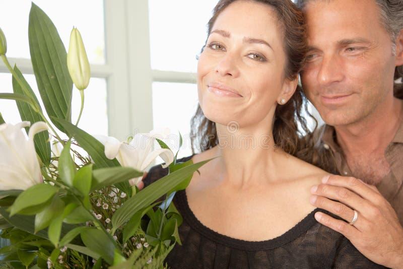 Homem que dá flores à mulher. fotografia de stock